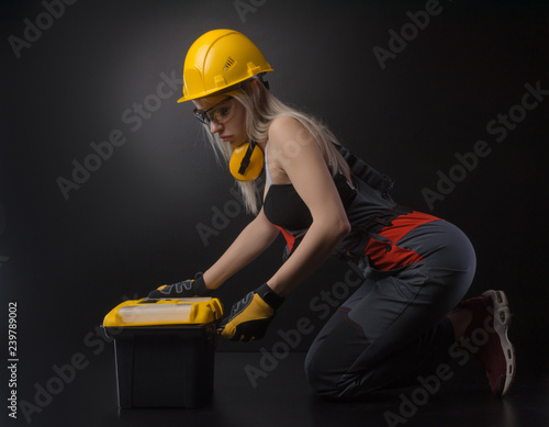 girl in overalls holding a suitcase with working tools