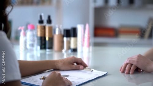 Photo Beautician filling clients card before appointing procedures, care for customers