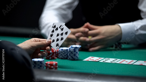 Tela Casino client having weak hand combination in poker making big bet with chips