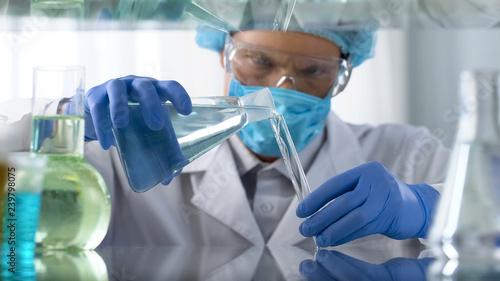 Fototapeta  Scientist in protective goggles pouring acid liquid into vial, dangerous tests