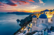 Leinwanddruck Bild - Beautiful view of Churches in Oia village, Santorini island in Greece at sunset, with dramatic sky.