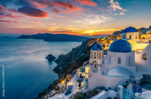 Tuinposter Lavendel Beautiful view of Churches in Oia village, Santorini island in Greece at sunset, with dramatic sky.