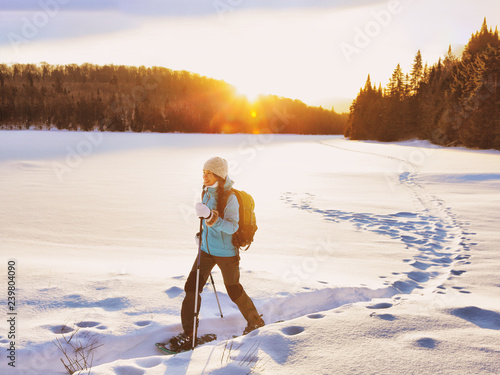 Spoed Foto op Canvas Wintersporten Winter sport woman hiking in snowshoes. Snowshoeing girl in the snow with shoe equipment for outdoor walking in forest trail. Quebec, Canada.