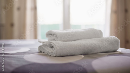 Hotel room with clean towels on fresh bed linen, accommodation service quality Canvas Print