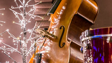 Close Up Of A Cello, Christmas Lights And Glitters Are In The Background.