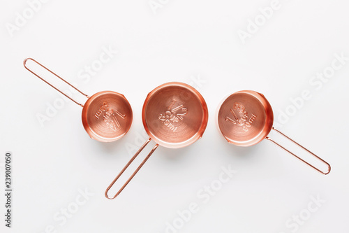 Fotografia Rose gold measuring cups on a white background, creative flat lay cooking concep