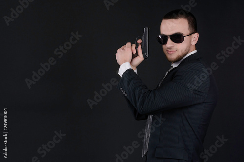Photo  Man in black suit and sunglasses hold a gun in his hand