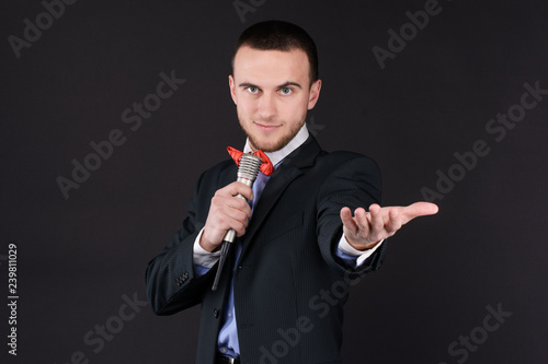 Photo  Handsome Master of ceremonies in black suit holding microphone in hand on black background