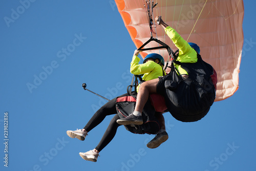 Wall Murals Sky sports Paraglider tandem fly against the blue sky, tandem paragliding guided by a pilot