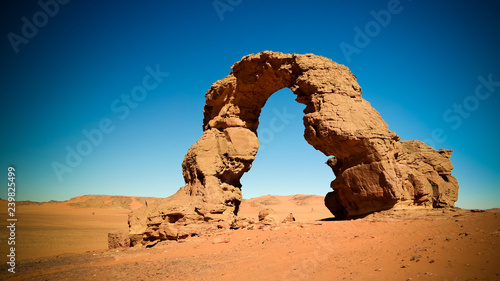 Arch Rock formation aka Arch of Africa or Arch of Algeria with moon at Tamezguida in Tassili nAjjer national park in Algeria