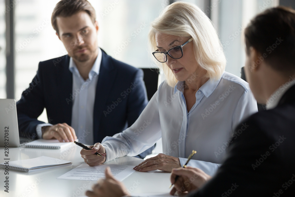 Fotografía Businessmen sitting at desk headed by middle aged serious concentrated female in eyeglasses checking agreement document before signing it