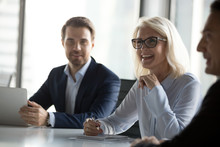 Successful Positive Businessmen And Businesswoman Sitting Negotiating In Boardroom. Middle Aged Woman Team Leader Discussing With Colleagues Share Ideas Solve Business Issues Feels Happy And Satisfied