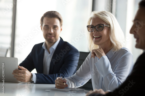 Fotomural  Successful positive businessmen and businesswoman sitting negotiating in boardroom