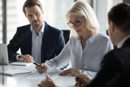 Valokuva  Businessmen sitting at desk headed by middle aged serious concentrated female in eyeglasses checking agreement document before signing it