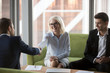 canvas print picture - Attractive smiling old business woman executive manager shaking hands with company partner greeting each other and expressing regard. Diverse businesspeople gathered together ready to signing contract