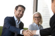 Leinwandbild Motiv Business people greeting each other at meeting, focus on handsome young confident businessman welcoming client. Aged female in eyeglasses, team leader and company partner handshaking in modern office