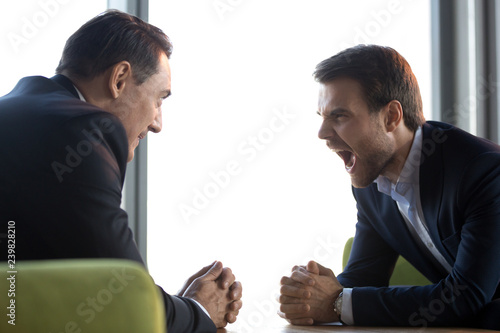 Different aged businessmen sitting on couch in office room face to face staring to each other Canvas Print