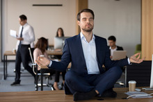 Business People Working In Coworking Space, Focus On Millennial Peaceful Employee In Formal Suit Sitting Without Shoes In Lotus Position On Office Desk Practising Meditation And Visualization Exercise