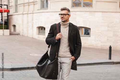 Handsome man wearing a coat walking