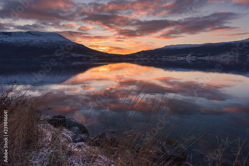 Deurstickers Canarische Eilanden Beautiful orange sunset sunset landscape with pink clouds in a fjord reflection in Norway near the city of Tromso with hoarfrost on the rocks near the ocean
