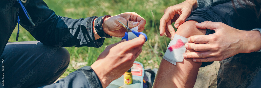 Fototapety, obrazy: Young man healing knee to a young woman who has been injured doing trekking