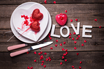 White plates in form of heart, cutlery, decorative hearts, candle  and word love on  vintage textured  background.