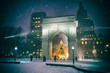 Leinwanddruck Bild - Winter holiday night view of the Washington Square Park with a Christmas tree under falling snow in New York City