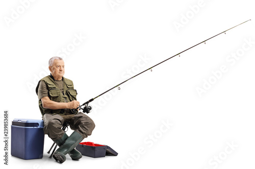 Photo Fisherman sitting on a chair with a fishing rod