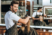 Handsome Young Hairstylist Smiling At Camera While Drying Hair To Beautiful Young Woman In Beauty Salon