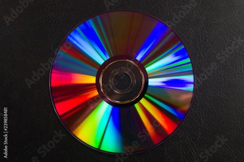 Valokuvatapetti Espectro de colores de luz reflejada por un disco DVD aislado sobre cuero repuja