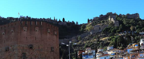 Fototapeta na wymiar Bedesten Alanya fortress. Big red bricks tower with residential buildings on background. Turkey.