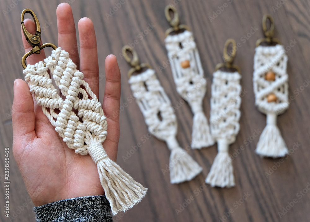 Fototapety, obrazy: Hand made cotton macrame key chain close up with four blurred in the background that have different styles and some have beads. The background is a beautiful wooden floor.