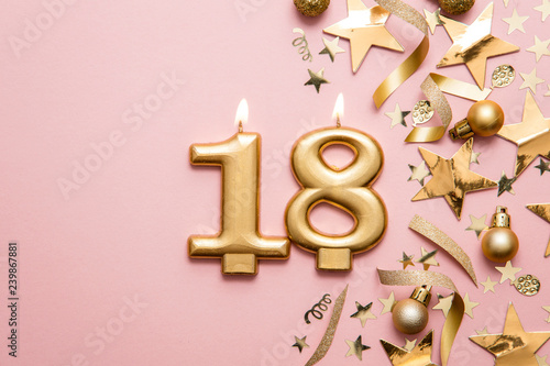 Photographie Number 18 gold celebration candle on star and glitter background