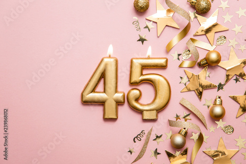 Photographie  Number 45 gold celebration candle on star and glitter background