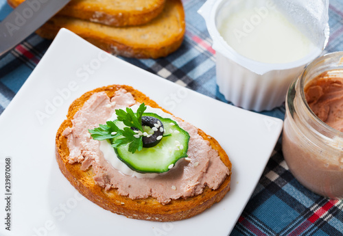 Pate on toasted bread with fresh cheese on white plate