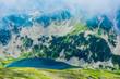 Beautiful foggy high mountains peaks, amazing lake, summertime. Alpine green fields, landscape.