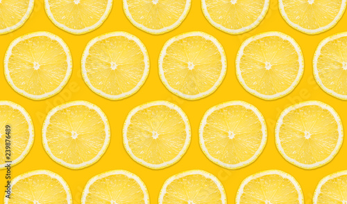 Yellow lemon slices pattern isolated on empty yellow surface with decorative shadow. Vibrant fruit background.