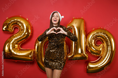 Fotografía  Merry young Santa girl in shiny glitter dress, Christmas hat celebrating holiday party isolated on bright red wall background, golden numbers air balloons studio portrait
