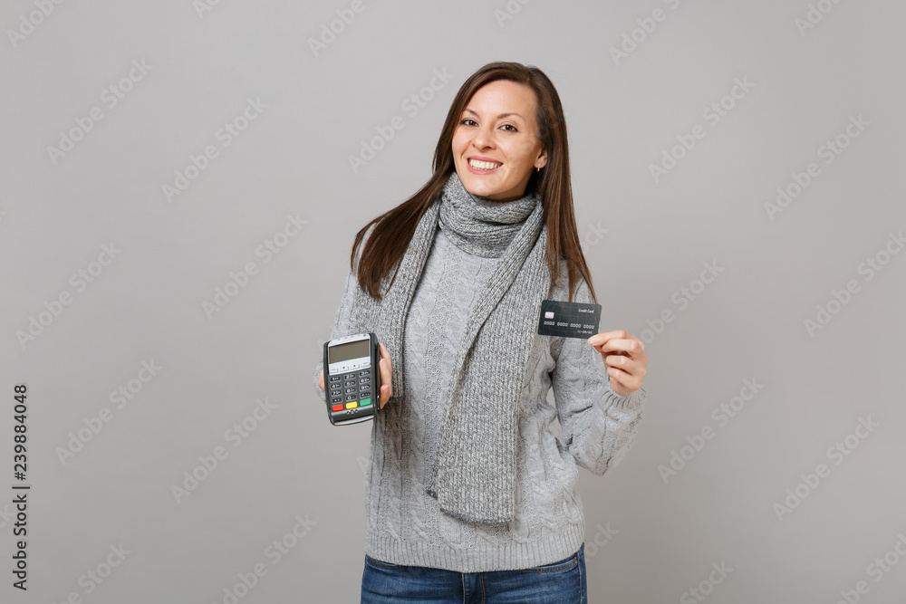 Fototapeta Smiling woman in sweater scarf hold wireless modern bank payment terminal to process, acquire credit card payments isolated on grey background. Lifestyle, people sincere emotions, cold season concept.