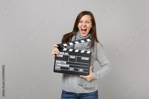 Fotografie, Obraz  Crazy young woman in gray sweater, scarf screaming, holding classic black film making clapperboard isolated on grey background