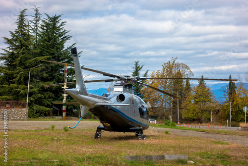 A helicopter stands on a clearing in the forest