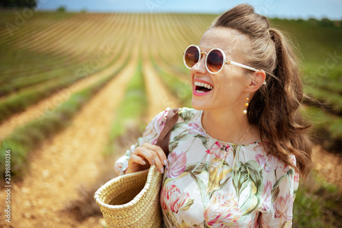 woman against green field looking into distance Wallpaper Mural