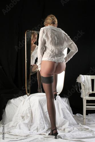 Zdjęcie XXL Kobieta w pończochach przed lustrem