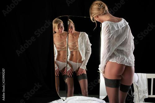 Fotografia  Frau in offener Bluse vor Spiegel