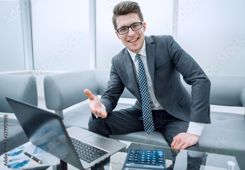 smiling businessman greeting you in his office