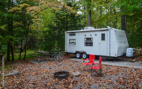Camping in camper trailer in wooded park camp site with chairs set up around fire pit, and bicycles leaning against picnic table.