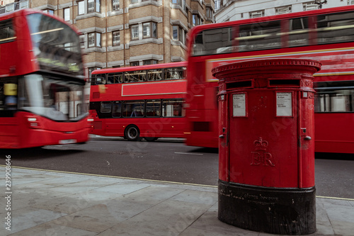 Fototapeta red mailbox in London with double decker bus passing by