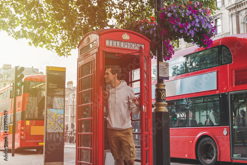 Fotografie, Obraz  young male in London looking out from a phone booth with red busses in the back
