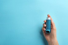 Woman Holding Asthma Inhaler On Color Background, Top View. Space For Text