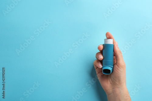 Photo Woman holding asthma inhaler on color background, top view